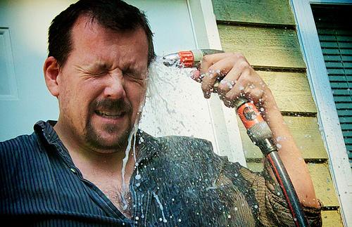 しかめっ面で頭に水をかけている男性